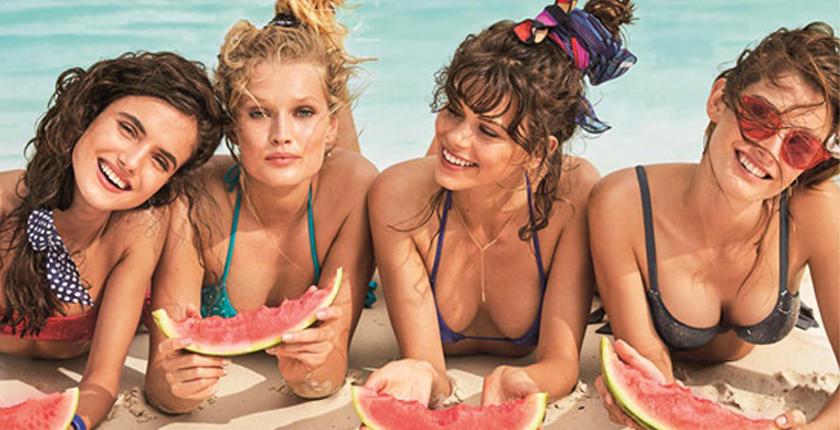 Chicas en la playa comiendo sandía