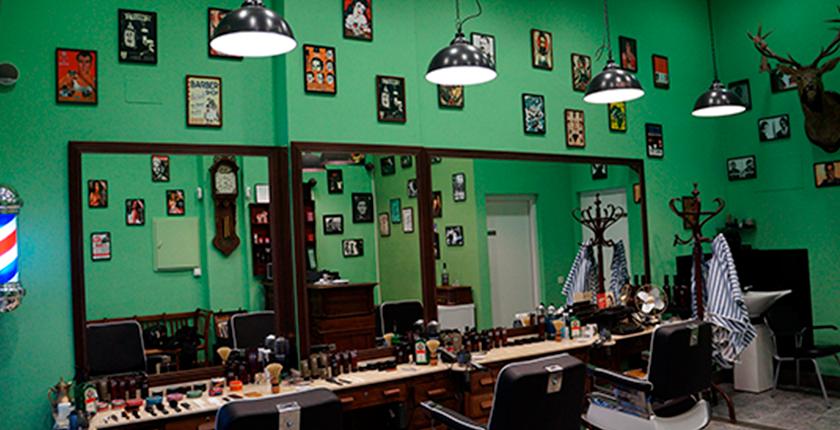 Barbería color verde con espejos y cuadros