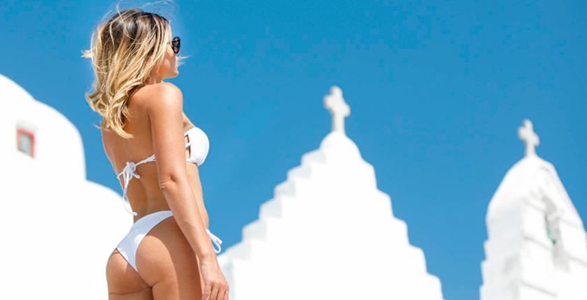 Tus bikinis favoritos chica en bikini blanco y cruz de fondo